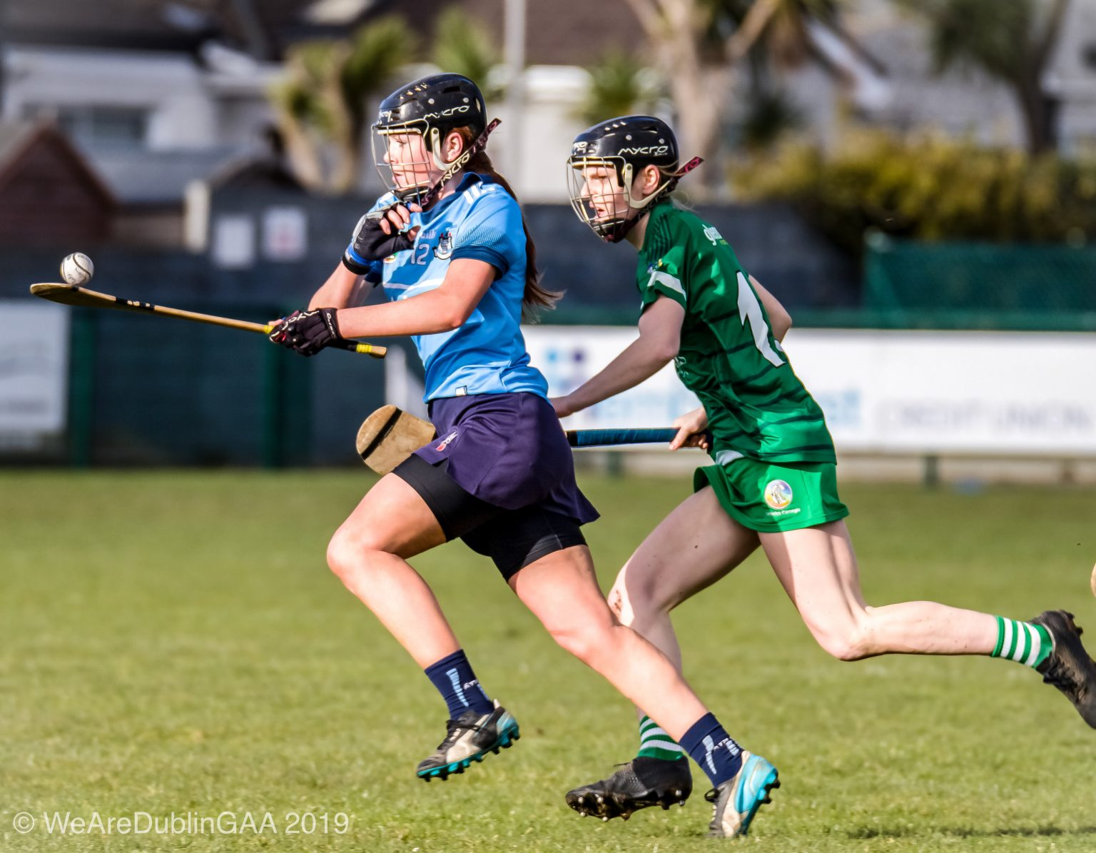 Dublin Camogie Player in a sky blue jersey, navy skort and Black Helmet races away balancing the ball on her girl from a Limerick player in a green Jersey and skort during the Littlewoods Ireland Camogie Leagues