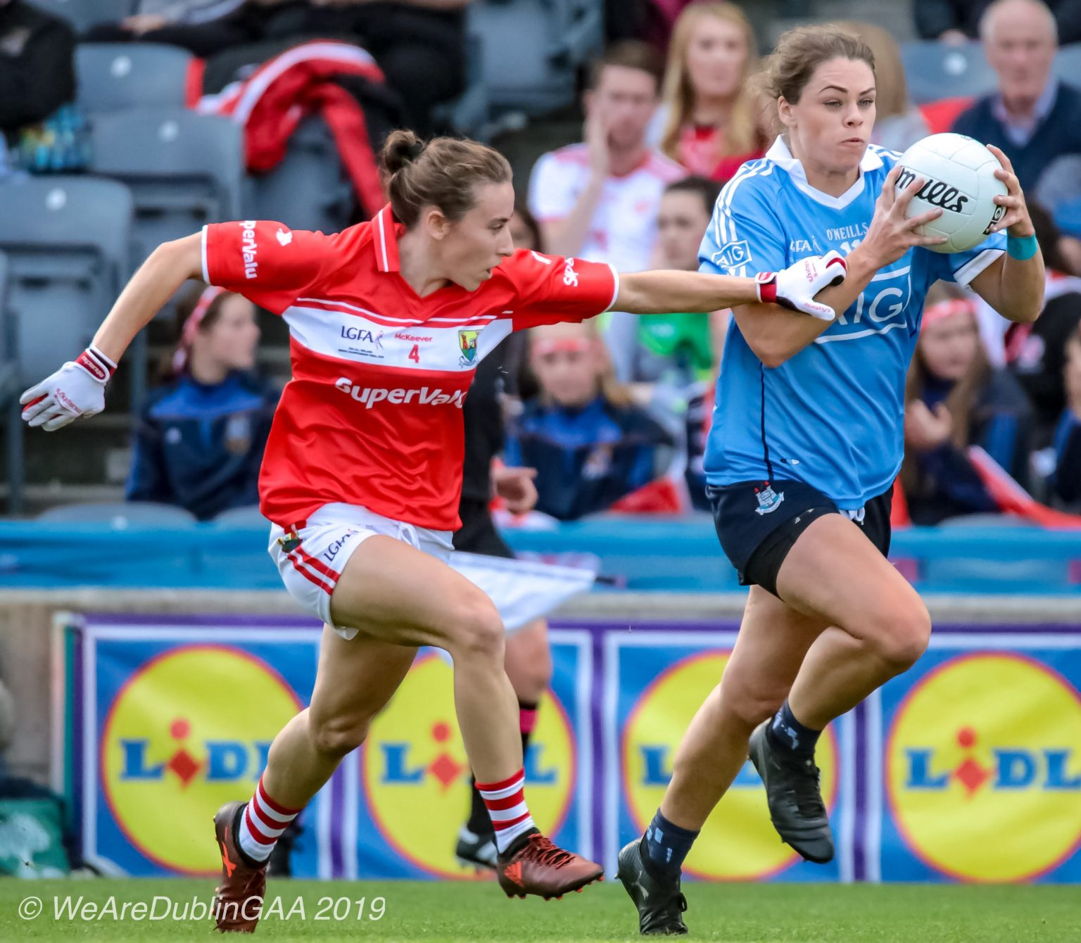 Dublin Ladies Footballer in a sky blue jersey and navy shorts raced away from a Cork player in a red jersey and white shorts the two teams meet in the league semi final and the LGFA will provide Facebook Live Coverage of the game.