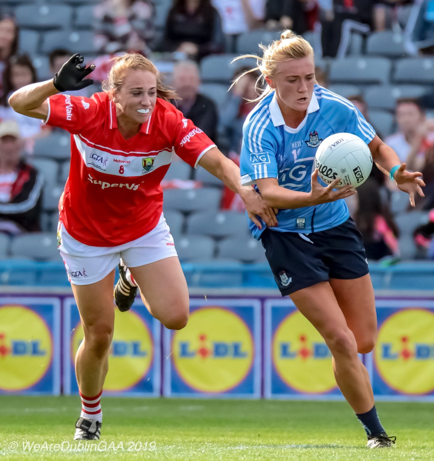 Dublin ladies footballer in a sky blue jersey and navy shorts gets away from a Cork player in a red jersey and white shorts in the 2018 All Ireland Final which was a game changer win for Dublin