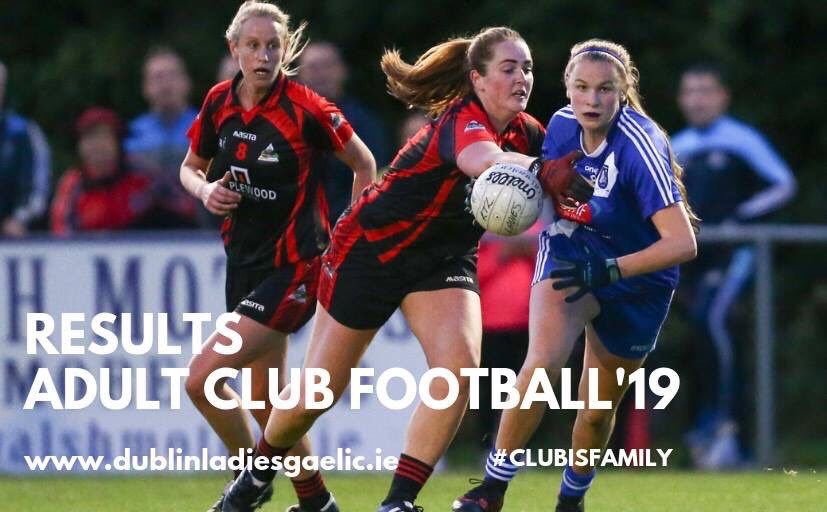 A Ladies footballer in a dark blue jersey and dark blue shorts battles for the ball with a player in a red and black jersey and black shorts with red stripes down the sides during the adult Club cup