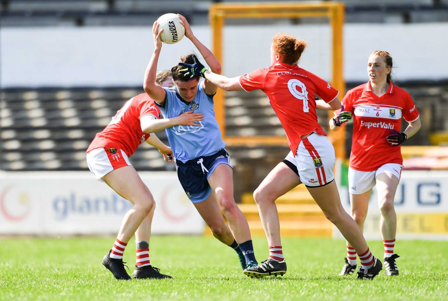 Dublin Ladies Footballer In a sky blue jersey and navy shorts is tackled by two Cork players in red jerseys and white shorts during the Lidl NFL Semi Final