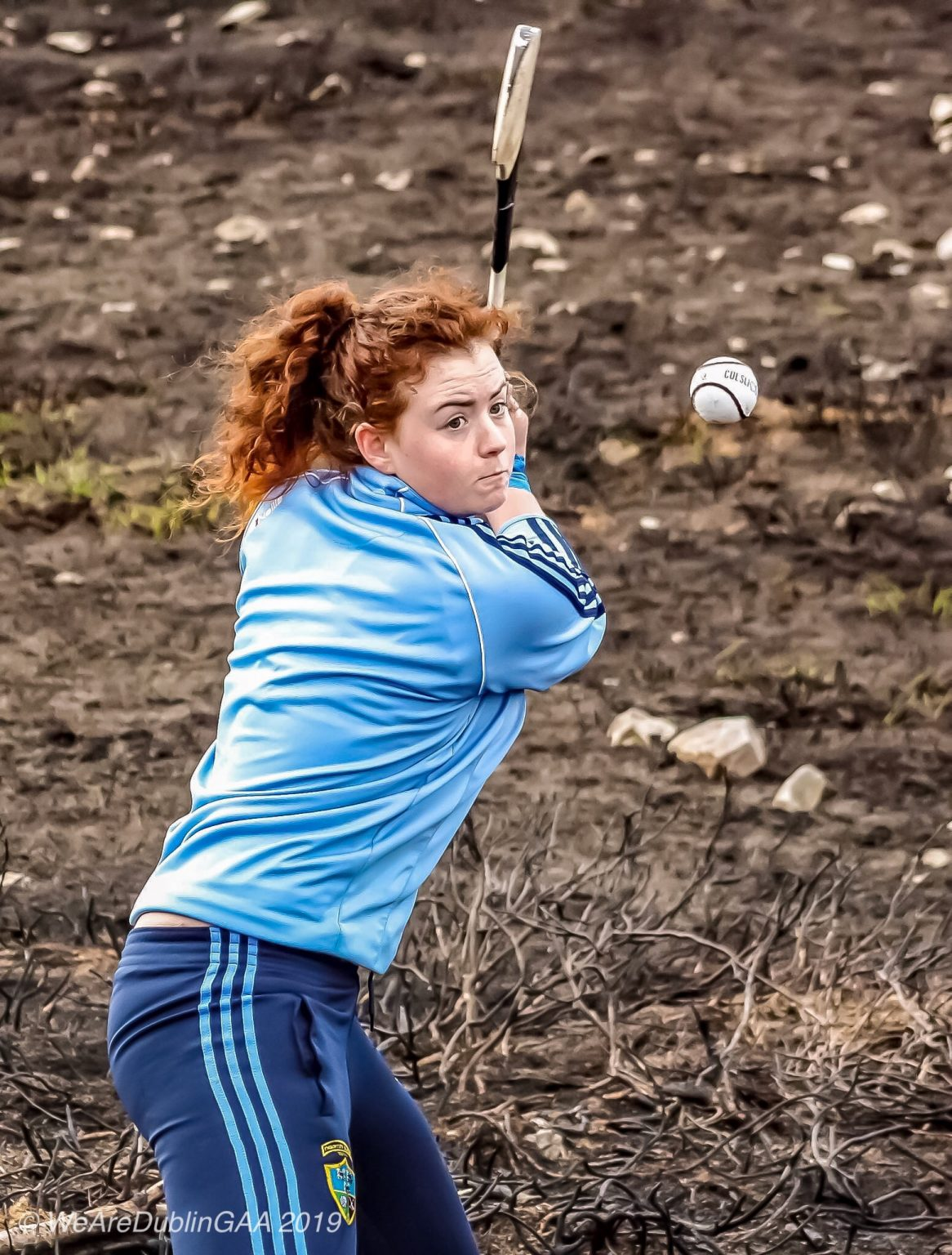 Dublin Camogie Goalkeeper Faye McCarthy In a light blue tracksuit top and navy bottoms just about to strike the ball with her hurl during the Dublin Camogie Poc Fada